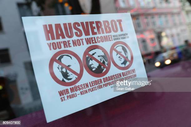 A sign in the window of a bar shows the faces of Russian President Vladimir Putin US President Donald Trump and Turkish President Recep Tayyip...