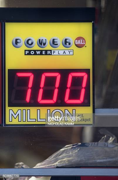 A sign in the window of a liquor store shows the Powerball lottery jackpot at $700 million in Washington DC on January 7 2016 The largest jackpot in...
