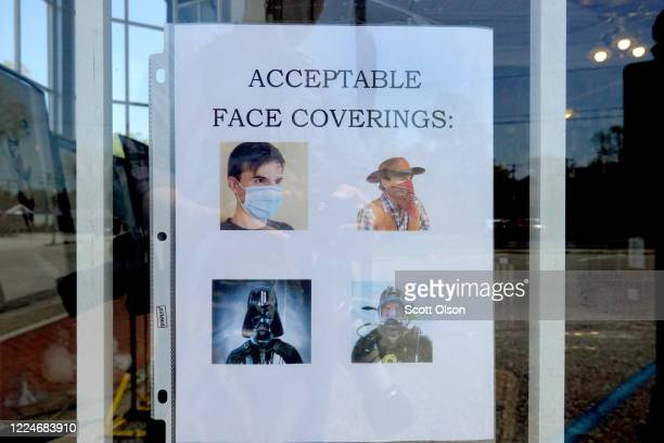 Sign in the window of the O'Gara and Wilson Antiquarian Booksellers bookstore asks customers entering the store to wear face masks on May 13, 2020 in...