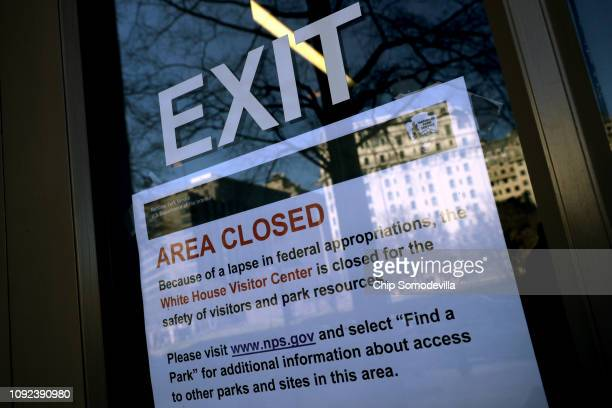 A sign in the window of the White House Visitors Center notifies visitors that it is closed due to the partial federal government shutdown January 10...