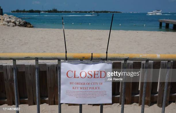 A sign indicates that a beach is closed as the city government takes steps to fight the coronavirus outbreak on March 25 2020 in Key West Florida...
