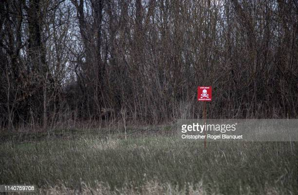 A sign indicates the presence of landmines on April 5 2019 in Opytne Ukraine Located between Donetsk and the frontline in Adviika Optyne has been...