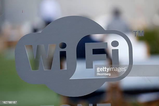 A sign indicating a free WiFi zone logo sits on the window of an exhibitor hall at the Mobile World Congress in Barcelona Spain on Wednesday Feb 27...