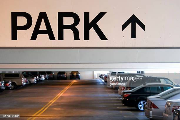 sign indicating parking lot on top of parking with cars - parking sign stock photos and pictures