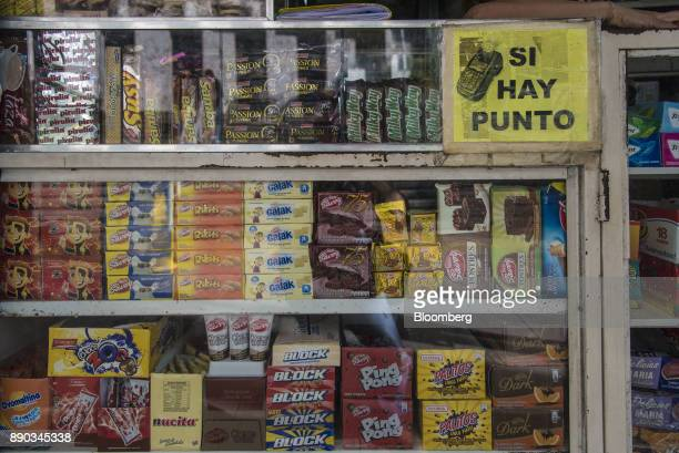 A sign indicating that credit cards are accepted is displayed in front of candy for sale at a stand at in the Chacao district of Caracas Venezuela on...