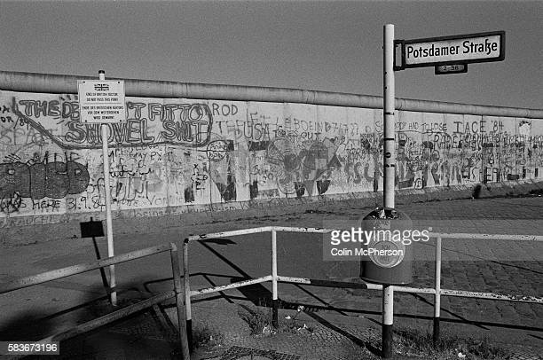 A sign indicating the end of the British sector next to the Berlin Wall at Potsdamer Platz West Berlin The Berlin Wall was a barrier constructed by...