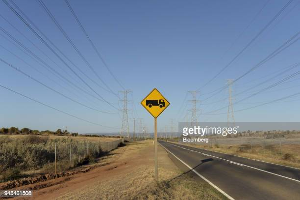 A sign indicating truck crossing or entering stands along a road as power lines hang from transmission towers on Torrens Island South Australia on...