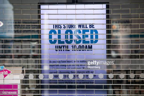 A sign informing customers of a late opening is displayed on an electronic screen in the shuttered window of a Carphone Warehouse operated by Dixons...