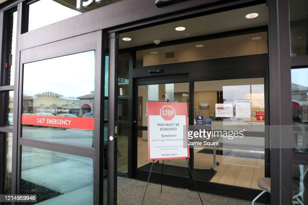 Sign informing patients that they must be screened before admittance at an emergency room is seen at a health clinic on March 26, 2020 in Kansas...