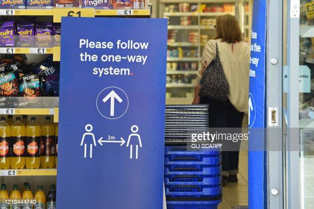 A sign instructing shoppers to maintain social distancing is seen at the entrance to a Tesco supermarket in Lincoln Eastern England on April 20 as...