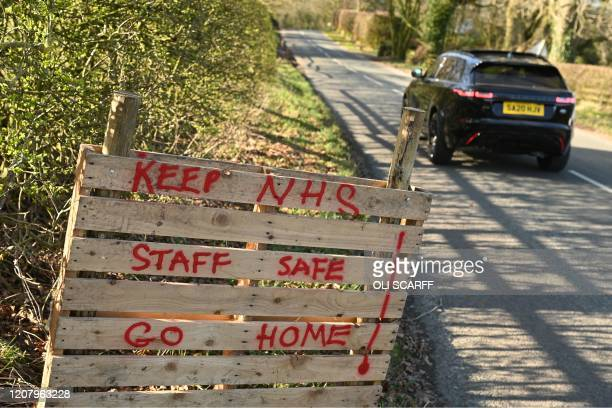 A sign instructing tourists to Go Home to protect our NHS staff is seen beside the road into Malham in northern England on March 22 2020 Up to 15...