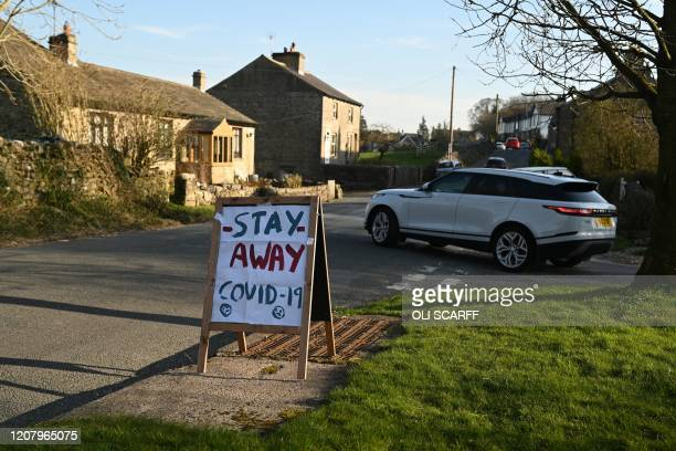 "Sign instructing tourists to ""Stay Away"" is seen beside the road in the village of Airton in northern England on March 22, 2020. - Up to 1.5 million..."