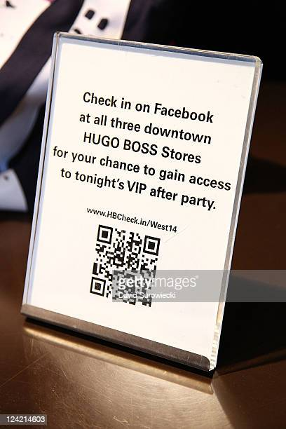 A sign instructs guests to check in on Facebook to the Hugo Boss store at 401 West 14th Street during Fashion's Night Out on September 8 2011 in New...
