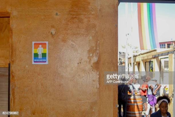 A sign is attached to a wall as people take part in the Namibian Lesbians Gay Bisexual and Transexual community pride Parade in the streets of the...