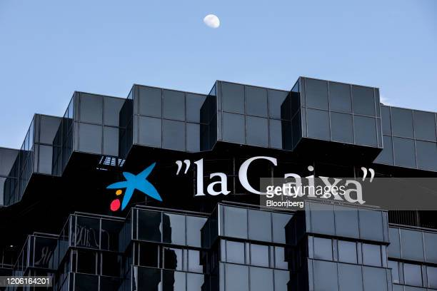 A sign is displayed by the top floor of the CaixaBank SA headquarters in Barcelona Spain on Thursday March 5 2020 Spanish bank shares soared after...