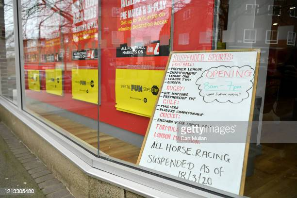 Sign is displayed in the window of a high street bookmakers listing the cancelled sports events on March 18, 2020 in Exeter, England. Coronavirus has...