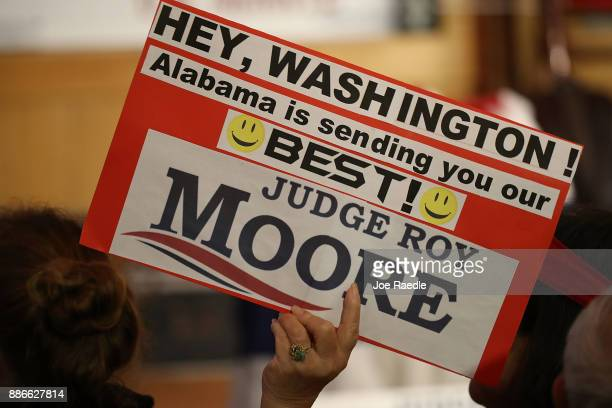 A sign is held up as people attend a campaign rally for Republican Senatorial candidate Roy Moore at Oak Hollow Farm on December 5 2017 in Fairhope...