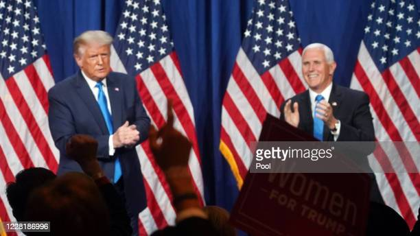 """Sign is held up saying """"Women For Trump"""" as U.S. President Donald Trump and Vice President Mike Pence clap in the backgroun on the first day of the..."""