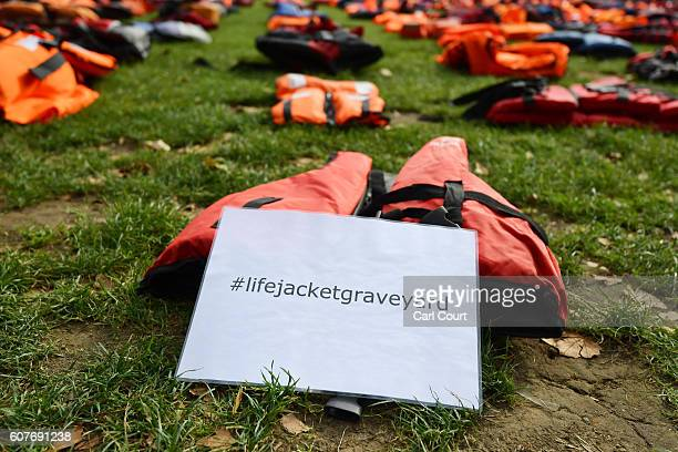 A sign is left with lifejackets that have been used by refugees to cross the sea to Europe are laid out in Parliament Square on September 19 2016 in...