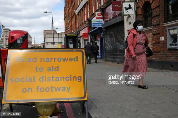 A sign is pictured explaining that the road has been narrowed to aid social distancing when using Camden High Street in central London on May 11 as...