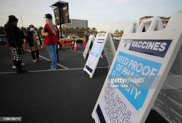 Sign is posted about proof of eligibility at a mass COVID-19 vaccination site in a parking lot for Disneyland Resort on January 13, 2021 in Anaheim,...