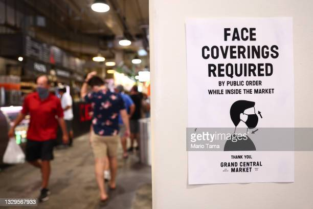 Sign is posted about required face coverings in Grand Central Market on July 19, 2021 in Los Angeles, California. A new mask mandate went into effect...