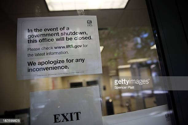 A sign is posted in the window of an IRS office in Brooklyn notifying that the office is closed due to the government shutdown on October 1 2013 in...