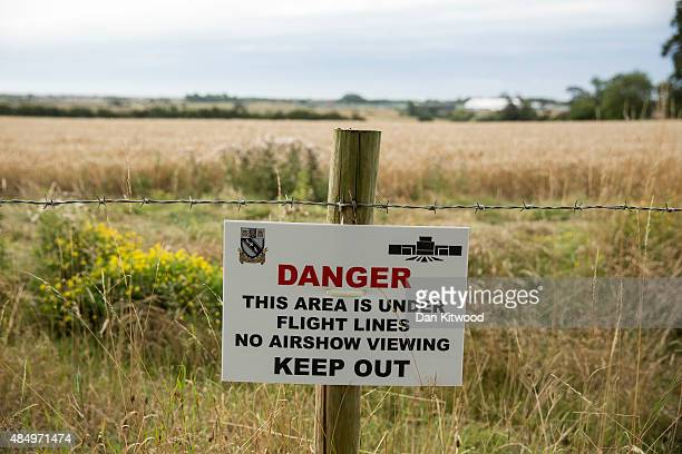 A sign is posted near farmland as emergency services and crash investigation officers work at the site where a Hawker Hunter fighter jet crashed on...