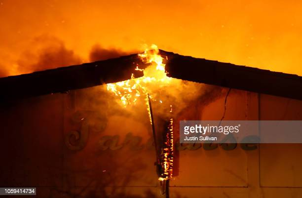 A sign is posted on the Paradise Skilled Nursing center as it is consumed by flames from the Camp Fire on November 8 2018 in Paradise California...