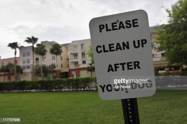 A sign is posted reading Please clean up after your dog' in The Village of Abacoa condominium complex where the condo association will begin testing...