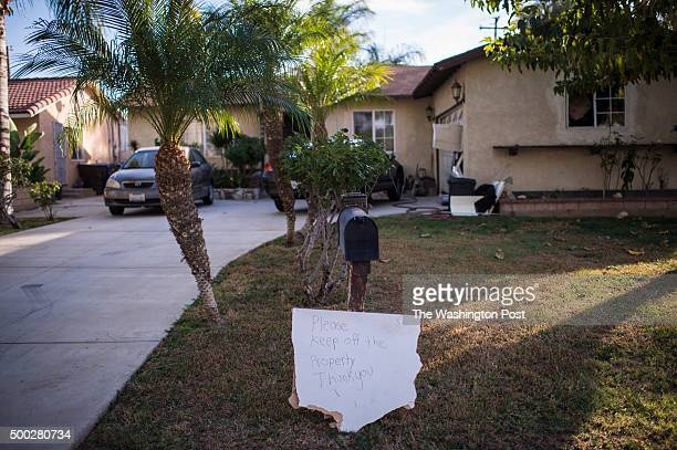 A sign is seen in the front yard after law enforcement officials raided the Riverside home of Enrique Marquez who lived next door to an old address...