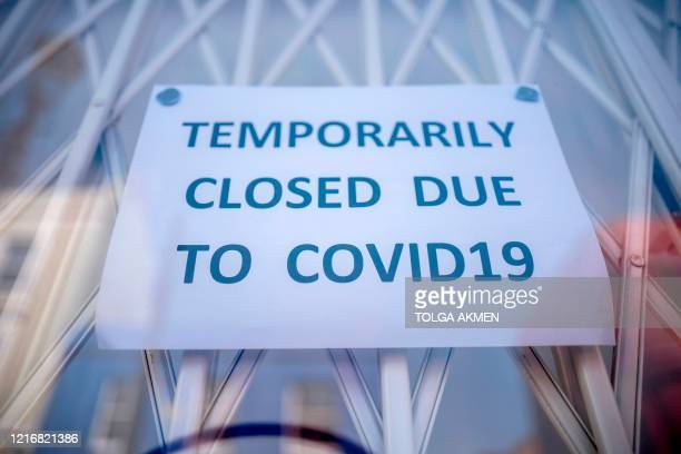Sign is seen in the window of a shop explaining to customers that it has temporarily closed due to the coronavirus outbreak in Portobello Market in...