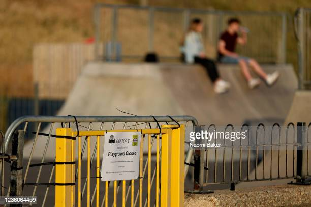 A sign is seen on a gate reading 'Playground Closed' as two teenagers sit inside the park on May 30 2020 in LeeOnTheSolent England The British...