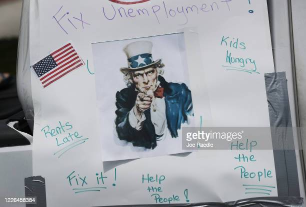 Sign is seen on a vehicle in a caravan protest asking the state of Florida to fix its unemployment system on May 22, 2020 in Miami Beach, Florida....