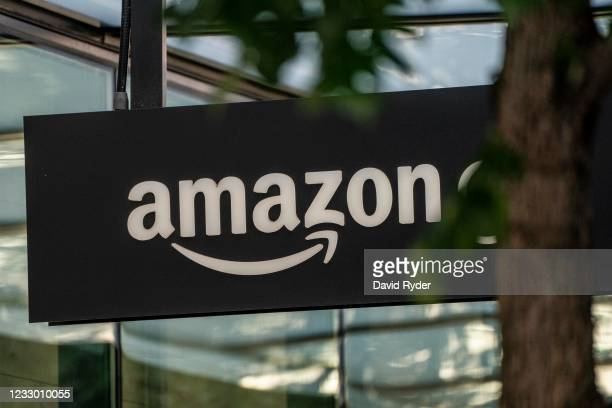 Sign is seen outside of an Amazon Go store at the Amazon.com Inc. Headquarters on May 20, 2021 in Seattle, Washington. Five women employees sued...