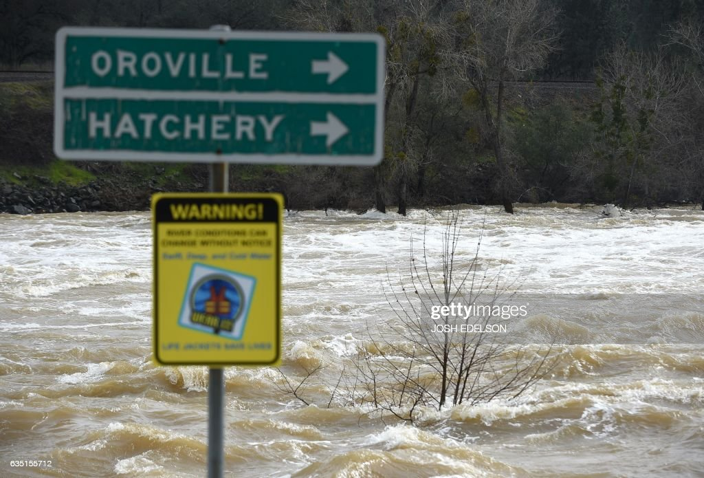 A sign is seen submerged by flowing water near Oroville, California on February 13, 2017. Almost 200,000 people were under evacuation orders in northern California Monday after a threat of catastrophic failure at the United States' tallest dam. Officials said the threat had subsided for the moment as water levels at the Oroville Dam, 75 miles (120 kilometers) north of Sacramento, have eased. But people were still being told to stay out of the area. / AFP / Josh Edelson