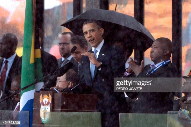 A sign language interpreter gestures as US President Barack Obama delivers a speech during the memorial service for late South African President...