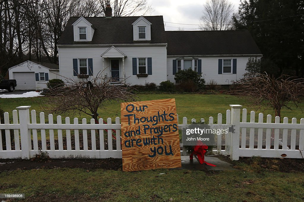 A sign leans against a home's picket fence near Sandy Hook Elementary School on January 14, 2013 in Newtown, Connecticut. The town marked a month anniversay since the massacre of 26 children and adults at the school, the second-worst such shooting in U.S. history.