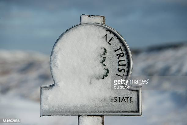 A sign marking the boundary of National Trust land is covered with snow near Standedge summit above the village of Marsden northern England on...
