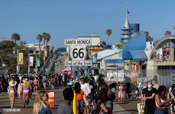 Sign marks the end of the historic route 66 as people walk on the Santa Monica Pier on April 30, 2021 in Santa Monica, California.