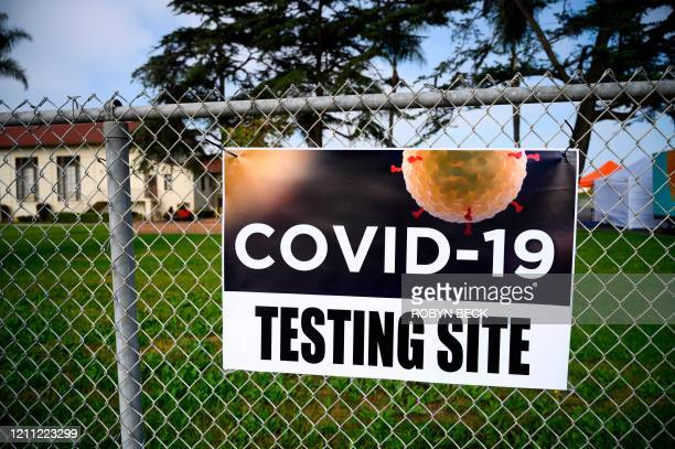 Sign marks the location of a COVID-19 mobile testing station in a public school parking area in Compton, California, just south of Los Angeles, on...