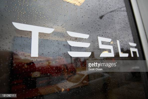 A sign marks the location of a Tesla dealership on ...