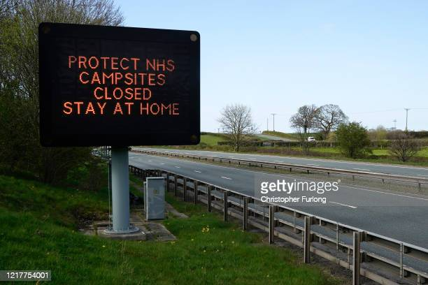 A sign next to the A55 main road into North Wales implores tourists to stay home and that campsites are closed during the pandemic lockdown on April...