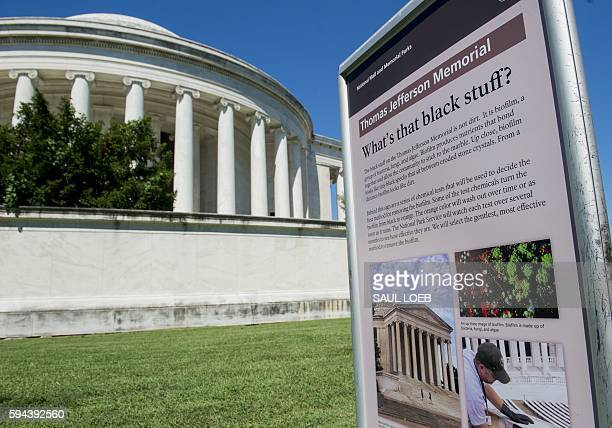 A sign next to the Jefferson Memorial explains that a black substance known as biofilm a group of bacteria fungi and algae covers the memorial in...
