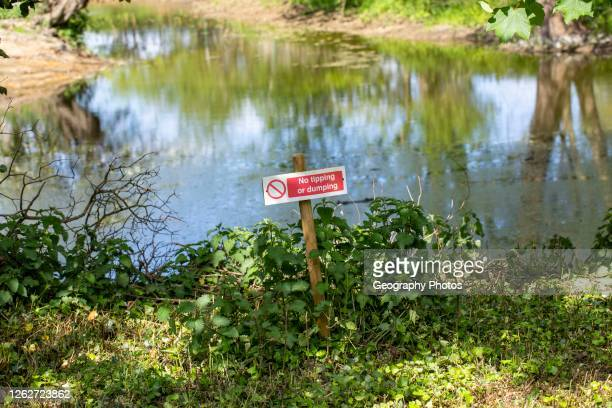 Sign No Tipping or Dumping next to pool of water, UK.