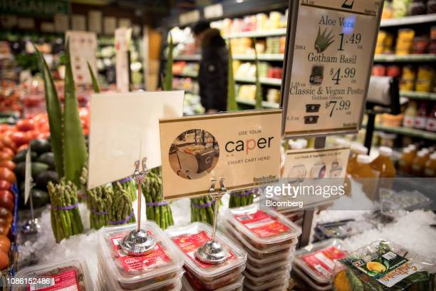 A sign notifies customers of Caper Inc smart shopping carts available for use at a Foodcellar Co grocery store in the Long Island City neighborhood...