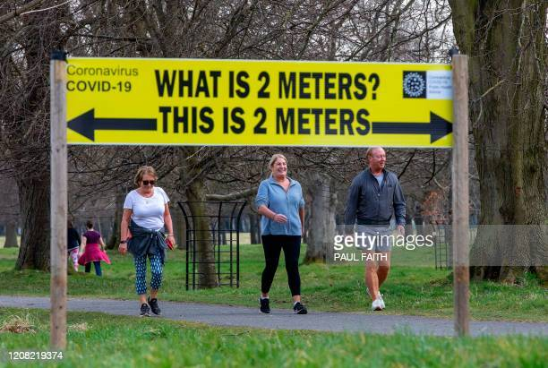 A sign notifies passers by of the 2 meter social distancing measures in place as people exercise in Phoenix Park in Dublin on March 25 after Ireland...