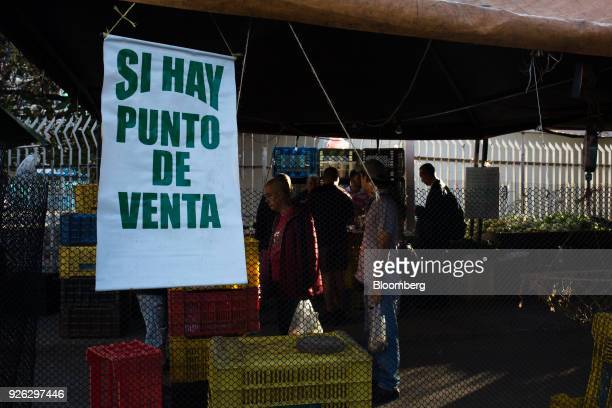 A sign notifying customers that they accept debit cards hangs on display outside a vegetable stand in Caracas Venezuela on Thursday March 1 2018...
