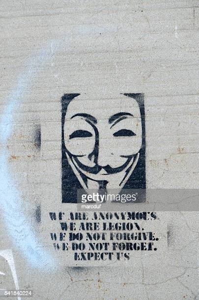 sign of anonymous painted on a concrete street - campaigner stock pictures, royalty-free photos & images