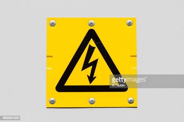 sign of danger high voltage symbol on the white wall - gefahr stock-fotos und bilder